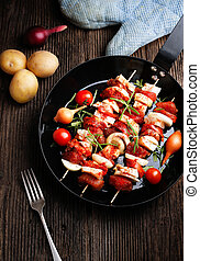 Vegetable and meat on wooden skewers on plate. Shish kebab...