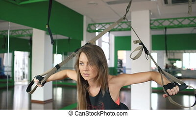 Young woman at the gym working on training arms with fitness straps in the gym
