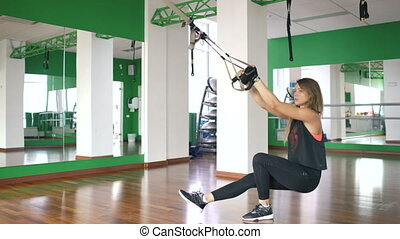 Young woman at the gym working on on trx and training legs with fitness straps in the gym