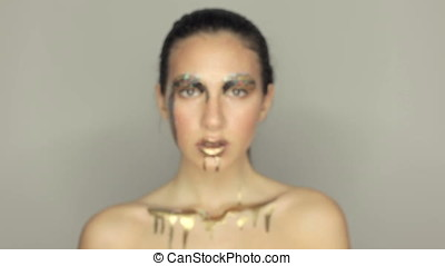 Beautiful model with amazinf conceptual gold make up posing...