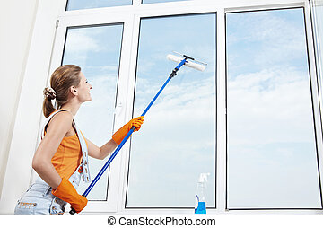 Cleaning - Attractive young girl washes windows