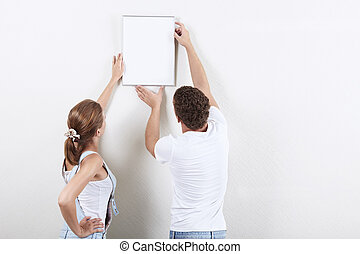Interior decoration - Young couple hanging up painting on...