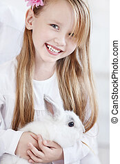 Happiness - The little girl holding a white rabbit
