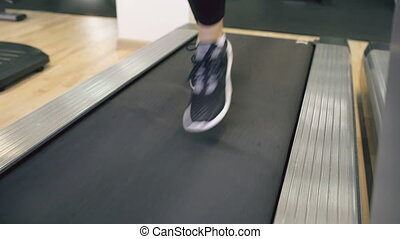 Closeup of woman feet in sneakers running on the treadmill at the gym