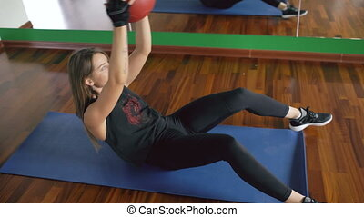 Attractive young muscular woman are working out with balls in fitness studio
