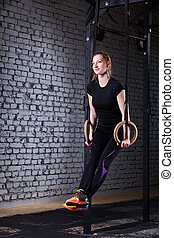 Young athletic woman doing pull-ups exercise with rings as cross fit workout against brick wall.