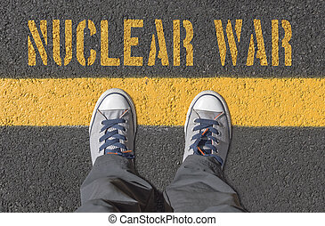 NUCLEAR WAR print with sneakers on asphalt road, top view.