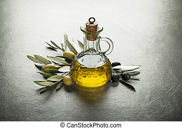 Olive oil and olive branch on the gray table