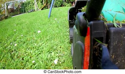 Lawnmower cutting grass in garden