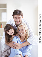 Laughing family - Young attractive family home on the couch