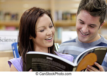 Cheerful couple reading a book in the science department of...