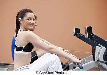 Happy woman with her boyfriend using a rower in a fitness...