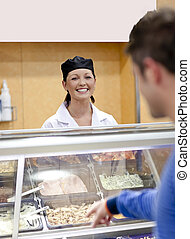 Cheerful female baker listening to a student in the queue of the cafeteria in the campus