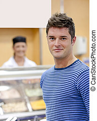 Portrait of a cheerful man choosing his lunch in the cafeteria