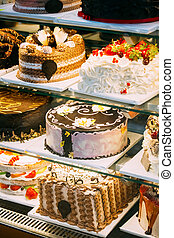 Different Various Types Of Sweet Cakes In Pastry Shop Glass Display