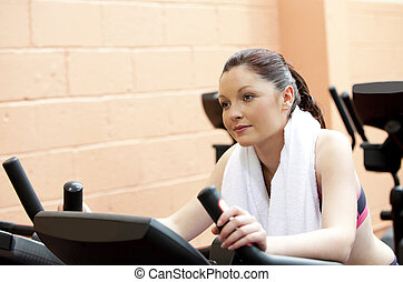 Beautiful woman training on a bicycle in a fitness center