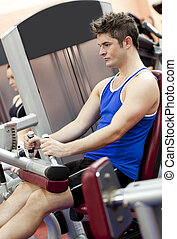 Serious athletic man using a leg press in the weights room...