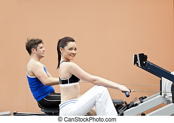 Positive woman with her boyfriend using a rower in a sport...