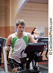 Handsome man doing exercises using a cross trainer in a...