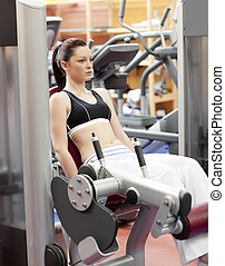 Attractive woman lifting weights with a leg press in the...