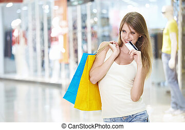 Shopaholic - A pretty young girl with a credit card in a...