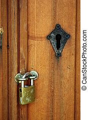 Padlock on old wooden door with black keyhole.