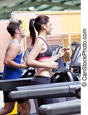 Pretty woman with earphones using a treadmill with her...