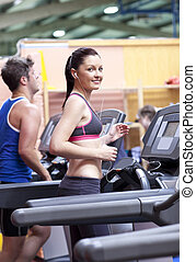 Athletic woman listening to the music while using a treadmill in a sport centre with her boyfriend