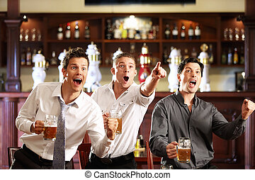 Fans at the pub - Three men with beer rejoice the victory of...