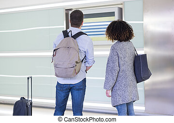 Young couple checking the timetable in a station - Young...