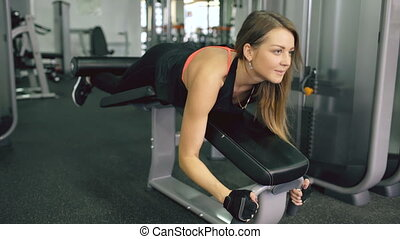 Young sporty woman doing exercises in the gym centre