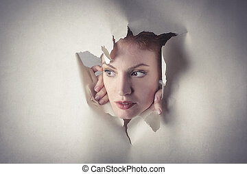Woman peeping out of paper