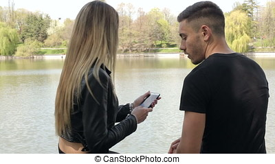 Girlfriend showing to her boyfriend something on phone