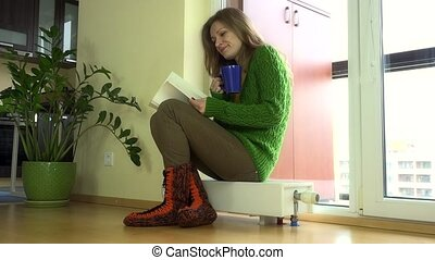 Lovely woman with tea pot and book sitting on warm radiator...