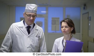 Two doctors in hall of hospital. Two senior doctors in special uniform walking in hall of hospital and having conversation.