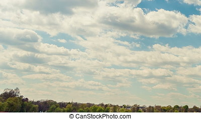 Timelapse of moving clouds over a park from city
