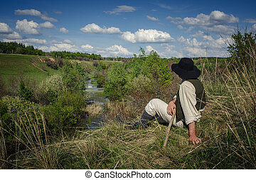 man sits on a hill near the river - man in a black hat sits...