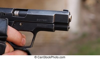 Shot from the gun. - Closeup of the muzzle of the pistol in...