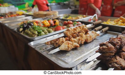 Barbecue meat on the pan. Grilled chicken and vegetables at the market. Barbecue chicken on skewers. A lot of grilled food. Shashlik. Zooming camera.