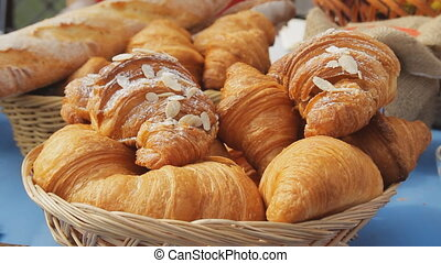 Sweet croissants in a basket on the table. Breakfast background with almond croissants. Delicious fresh croissants, close-up