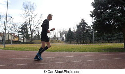 Slow motion view of man starting to jog on the course track