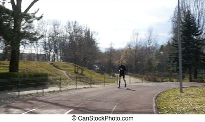 Man jogging in the park on the course track with closeup...