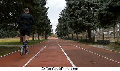 Back view of man jogging in slow motion on a course track