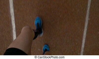 POV - Point of view of jogger feet running on course track...