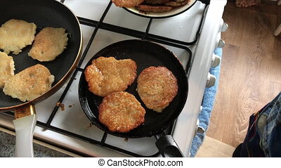 Preparation of potato pancakes. Pancakes are fried in two pans. View from above. Video shot on the iPhone 7 Plus.