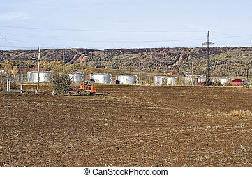 Tanks and tractor - Silvery-gray oil storage tanks, red...