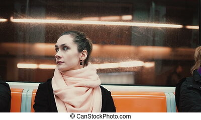 Young beautiful woman sitting in subway. Attractive...