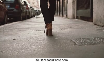 Close-up view of stylish woman walking in little street....