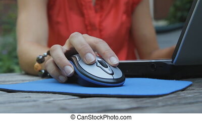 Female hand operates computer mouse