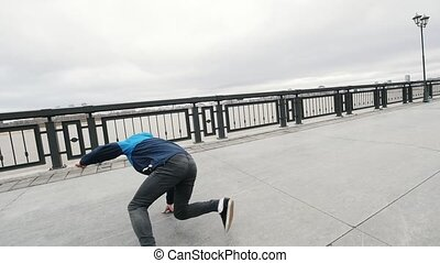 Teenager performing some flexible breakdancing at promenade,...